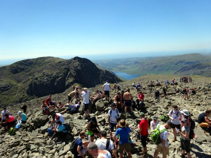 Crowds of people on top of Scafell Pike, the highest point in England, with Sca Fell and Wast Water behind