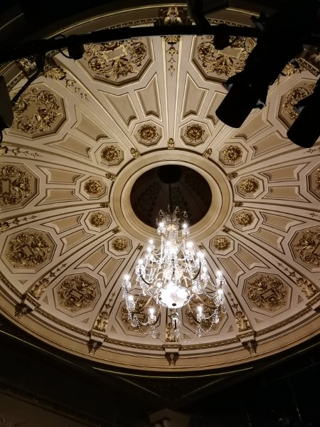 A chandelier was suspended above the auditorium like a giant serac of death