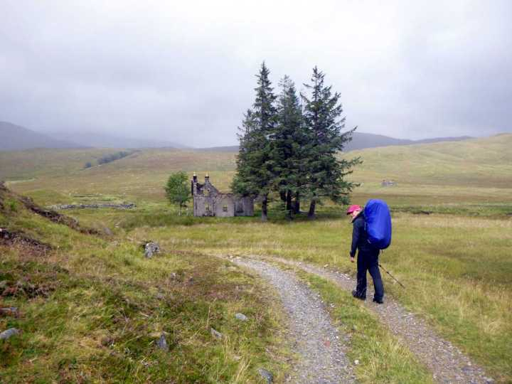 Edita approaches the abandoned building and copse of trees at Luibeilt. The river flows past right behind them and Meanach bothy can be seen to the right of the trees on the far shore.