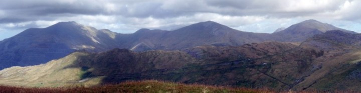 Panorama of some Welsh 3000ers from Moel Cynghorion: Elidir Fawr (924m), Y Garn (947m), Tryfan (915m, peeping up behind), and Glyder Fawr (999m). The Llanberis Path and Snowdon Mountain Railway run across the hillside in the foreground.