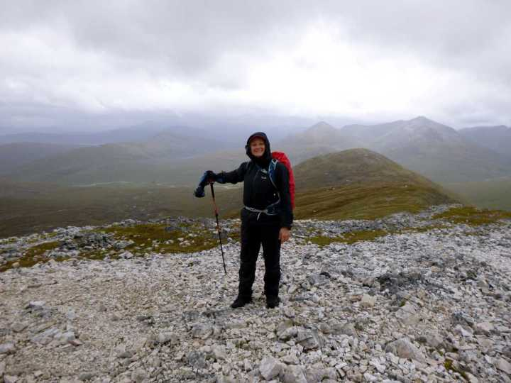 Edita on the summit of Stob Ban, pointing down towards the five lonely trees that mark our campsite. The eastern Mamores are behind her left shoulder.
