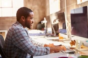 man working at computer via shutterstock