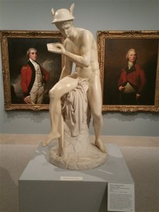 A Sculpture of Mercury among 18th century portraits at the Museum of Fine Art