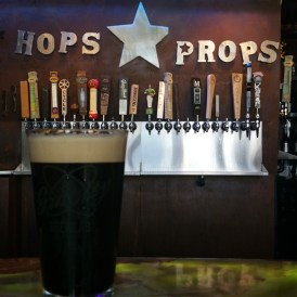 A pint of beer in front of the tap handles at Hops and Props in St. Petersburg, Florida