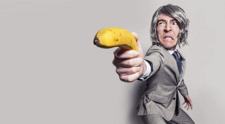 Mann im Business-Anzug mit Bananen-Pistole