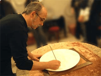 Mark Walford, potter, signing one of his plates