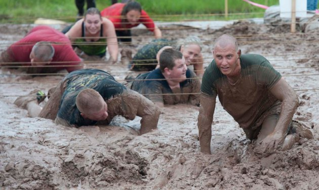Participants in the Marquette Mountain Mud Run crawl on their bellies through a mud pit as they near the finish line. (photo by Ron Caspi)