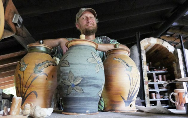 Ryan Dalman poses with some of his Wood Fired Pottery in Michigan's Upper Peninsula. (photo by Ron Caspi)