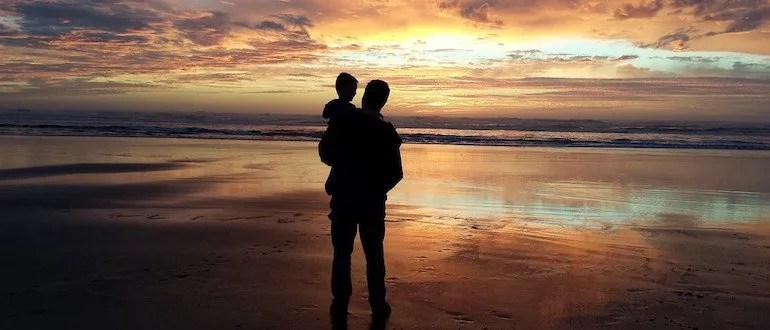 Father and son standing on the beach with sunset