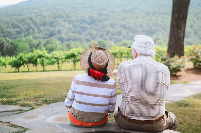 An older couple sitting outside on a beautiful day