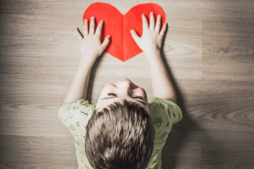 Child holding red heart