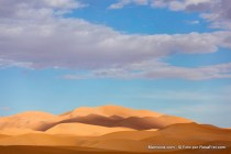 Erg Chebbi sand dunes with cloudy blue sky in the Sahara desert of Morocco.