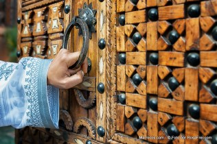 A hand holding a door handle of a traditional, wooden, moroccan door, Ouarzazate, Morocco.
