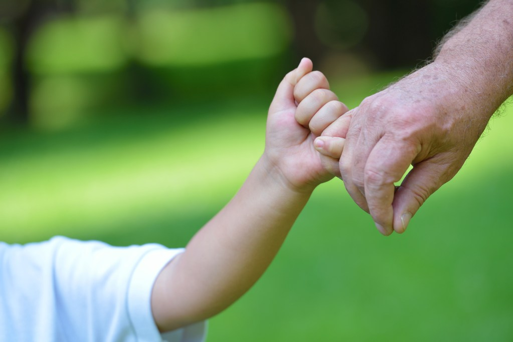 child and grandfather holding hands; planning for generations