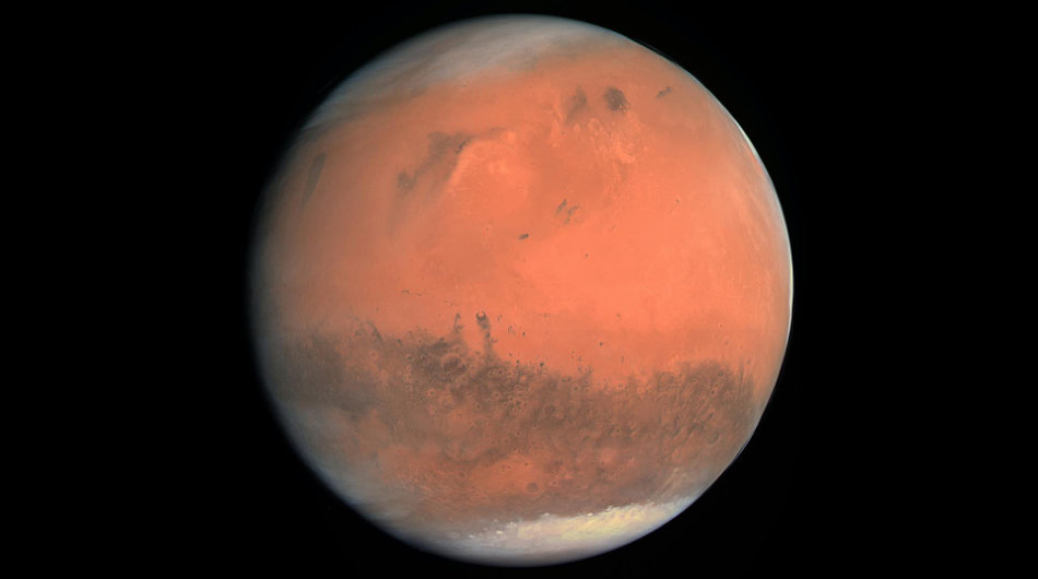Red planet Mars in space with polar ice caps visible