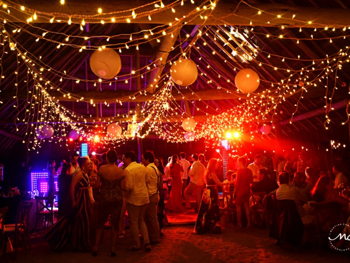 Packed dance floor with bistro lights at Blue Venado Weddings by Martina Campolo Photography