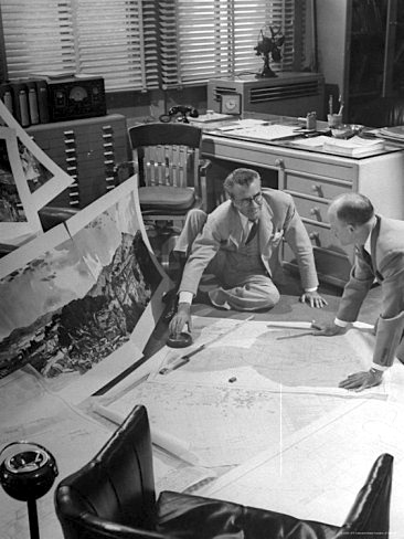 MGM art director, Cedric Gibbons, working on the floor of his office on the blueprints for the set of a movie
