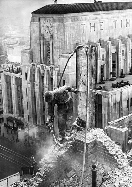 The new Los Angeles Times building rises behind a worker demolishing the paper's previous home, 1937