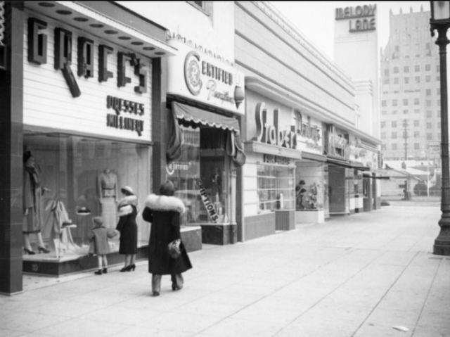 Shoppers walking down Wilshire, 1937 Graff's (dresses), Cerfitied Prescriptions, Staber (furs) and Melody Lane