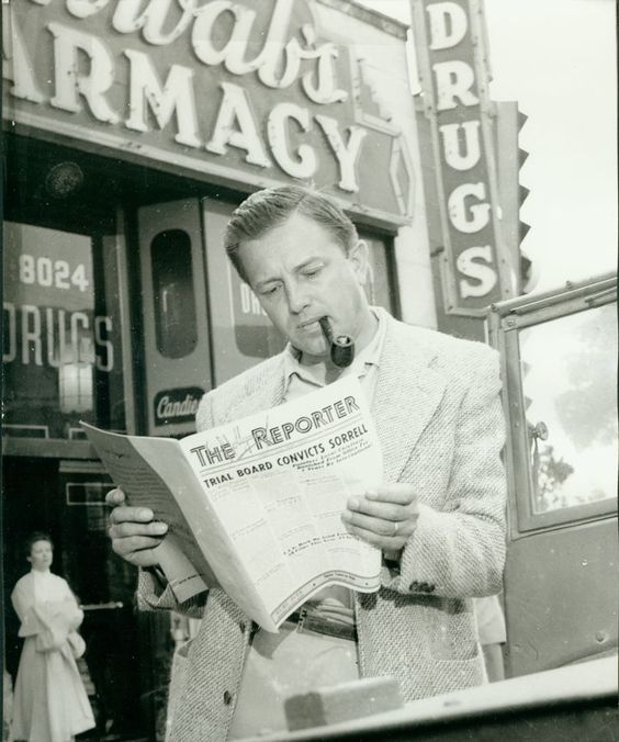 Movie director (The Caine Mutiny (1954)) reading The Hollywood Reporter outside Schwab's Pharmacy