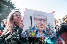 Leah Orton shares her rendering of Stephen Harper near the makeshift stage. On the reverse is a depiction of Christy Clark.