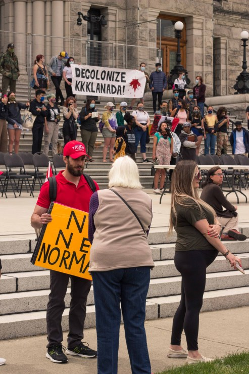 A person wearing a trump hat stands in front of the Resist Canada 153 group