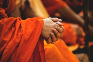praying monk in orange robe