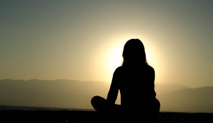 Woman sitting in lotus position at dusk