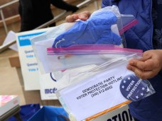 Shruti Bhatnagar holds packages of personal protective equipment and information about a Montgomery County Democratic Party voter protection hotline. The bags were given out to the parties volunteers at early voting centers throughout the county. Photo by Danielle E. Gaines.