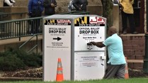 A voter drops his mail ballot off as others wait in line at the Show Place Arena in Prince George's County. Photo courtesy of Andre Matthews/Prince George's CTV News.