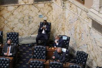 The pandemic yielded some unusual seating arrangements in the House chamber on the first day of session: Del. Tony Bridges (D-Baltimore City) sat in a tall chair — no desk — in a back corner, while 14 of his colleagues were spaced out in the public gallery above. Photo by Danielle E. Gaines.