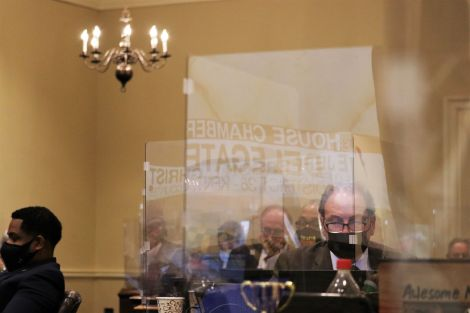 A screen projecting the House of Delegates floor reflects off of plexiglass barriers in the House Chamber Annex on Monday. Photo by Danielle E. Gaines.