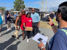 A campaign worker takes a photo of Democratic gubernatorial hopeful Wes Moore with attendees of the J. Millard Tawes Clam Bake and Crab Feast in Crisfield. Photo by Bruce DePuyt.