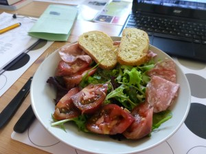 Lunch salad with tomato, olives, salami and bread