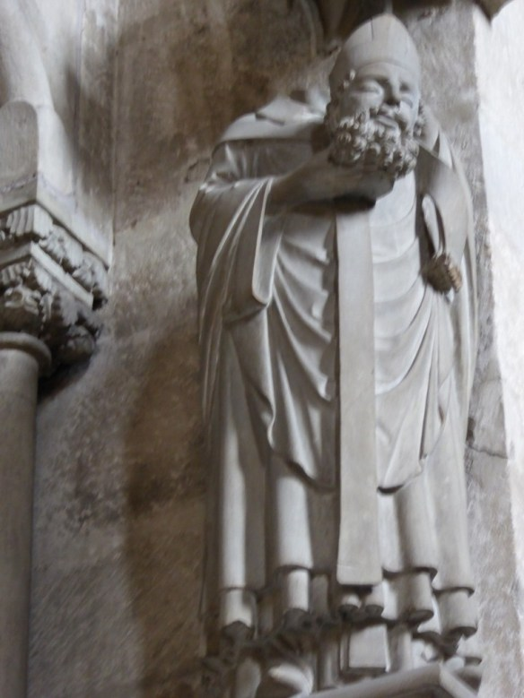 Statue of a cephalophore saint, maybe St. Denis? (a cephalophore is a being whose head has been chopped off but he walks around carrying it)