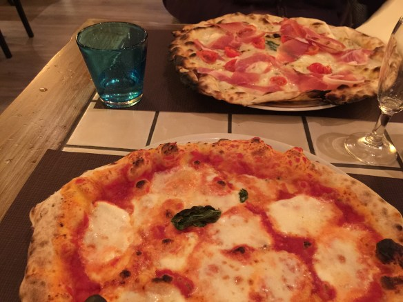 Foreground - pizza margherita verace, thin crust white pizza with proscuitto behind