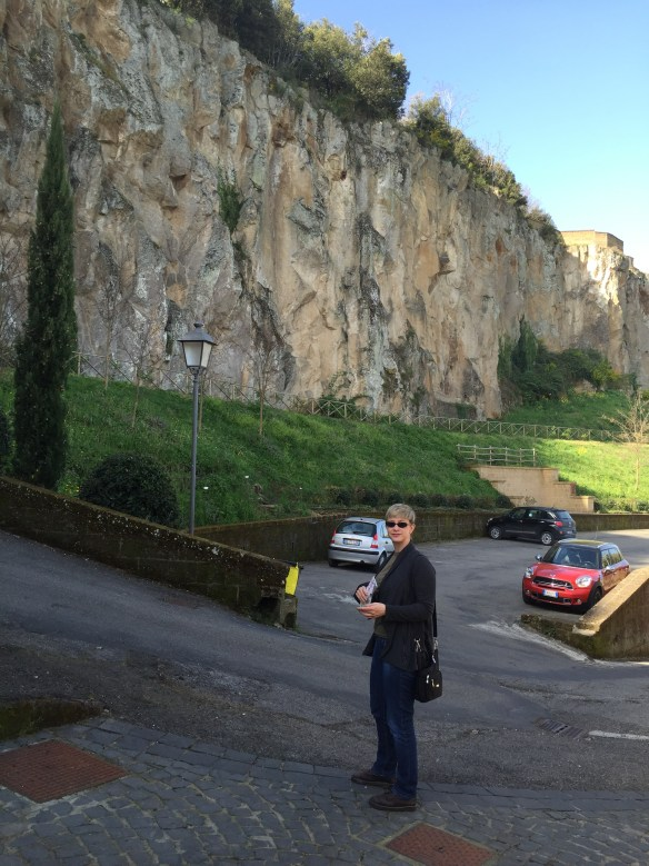 Sarah walking over to the hotel parking lot next to the enormous rock of Rocca Ripesena