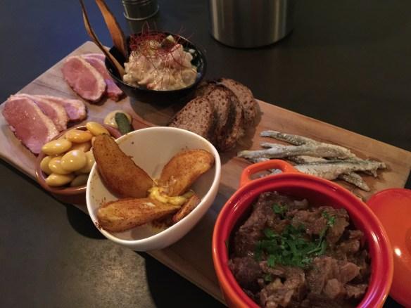 Clockwise - tuna ceviche, bread, anchovies, goat stew, crispy piri piri potatoes with saffron aioli, Lupini beans, and glazed duck breast