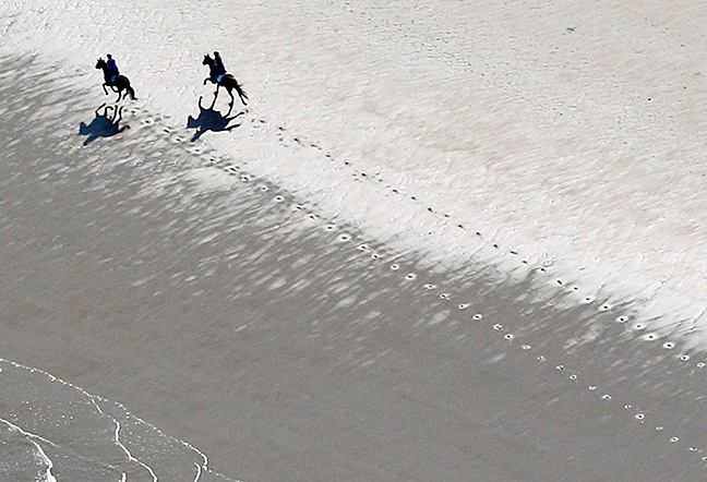 Horses gallop along Hampton Beach on a warm spring day.