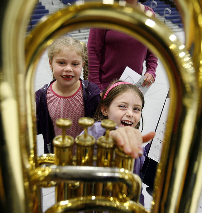 A Londonderry high school band member blows into a tuba as a smiling Amelie Fegan, 4, of Londonderry selects the note by pressing the valve as her sister Alyssa, 6, looks on at the Londonderry High School's Symphonic Band Music Fair and Concert.