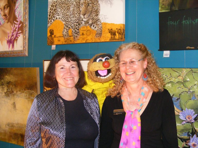 Bendigo Bank representatives Rae Gate (left) and Prue Sheehan admire the Open winning portrait, which won the bank's $2500 prize. Puppet personality Agro also made a surprise appearance at the awards night.
