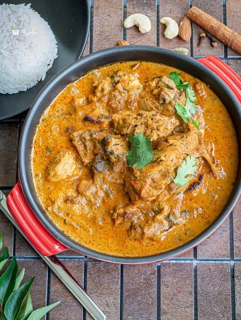 Chicken korma served in a red bowl with rice on the side.