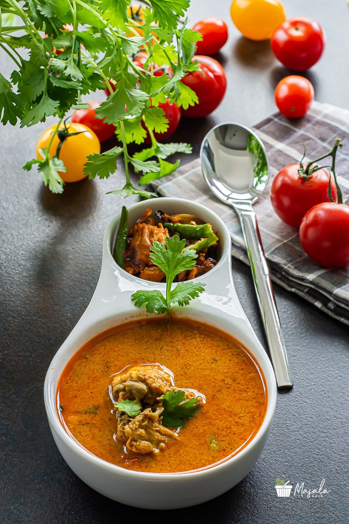 chicken rasam or indian style chicken soup with cherry tomatoes on the side.