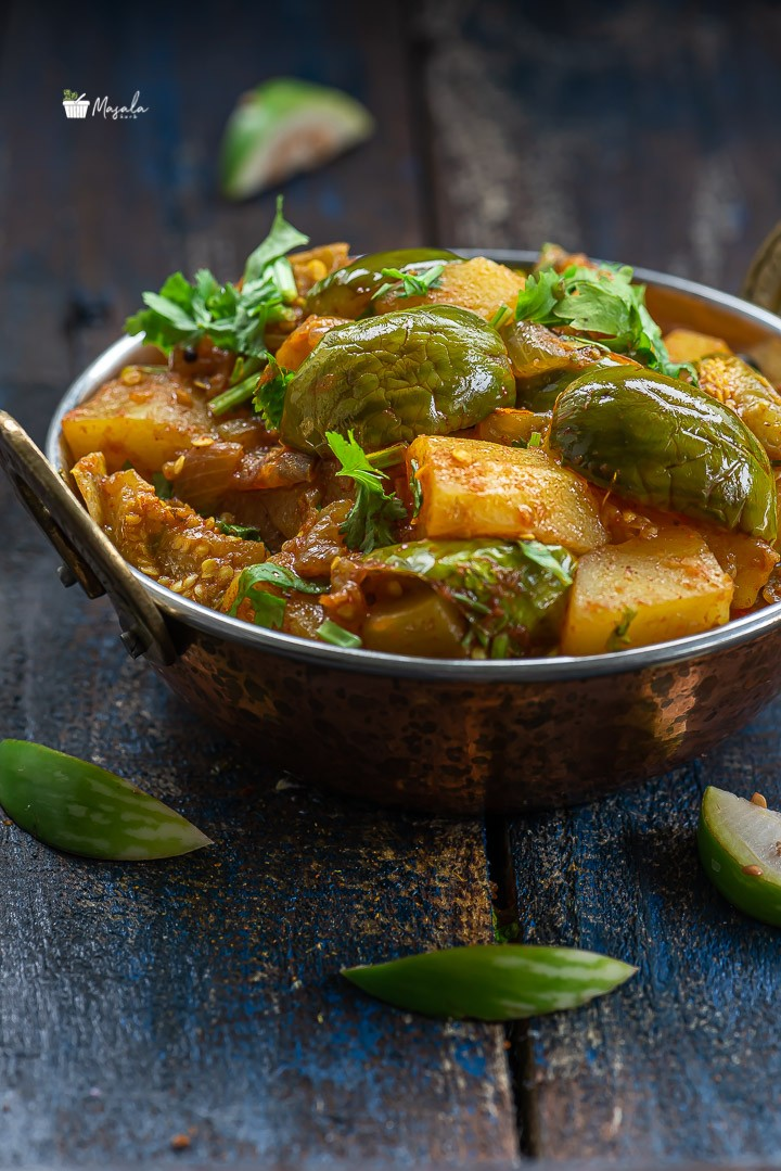 Close up view of aloo baingan sabzi/Green Eggplant Potato Curry.