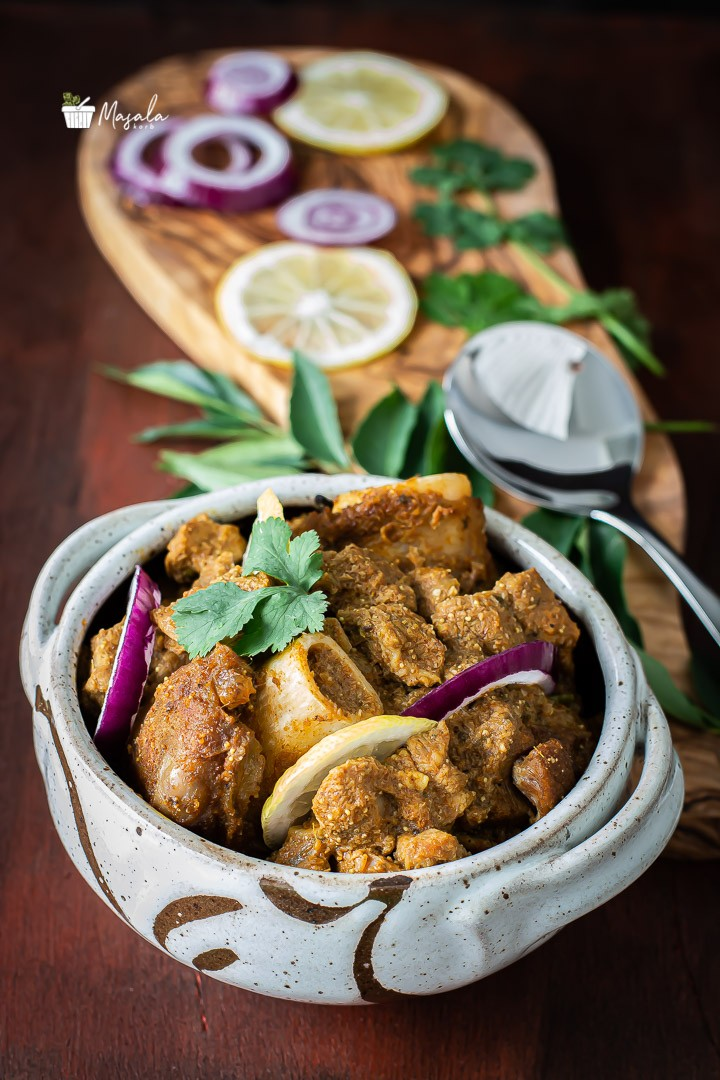 Muttton curry served with onion slices & lemon wedges.