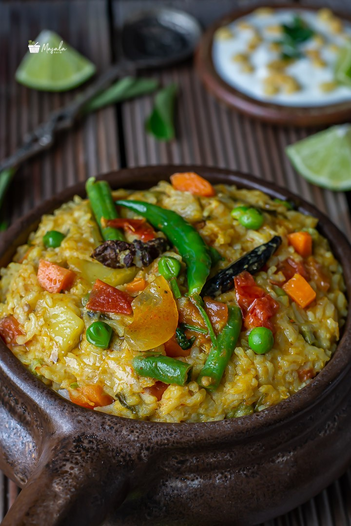 Close up view of khichdi with green chillies on top