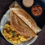 Barnyard Millet Dosa served on a bleck plate with potato masala and two chutneys.