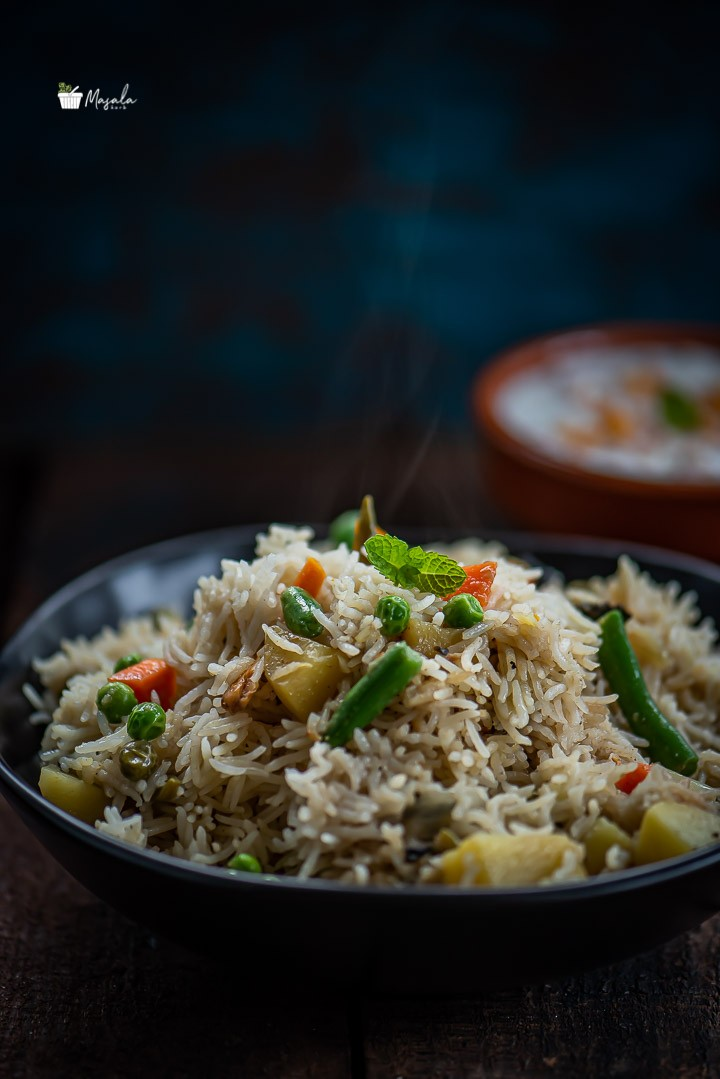 Close up shot of Instant Pot Vegetable Biryani served in a black bowl.