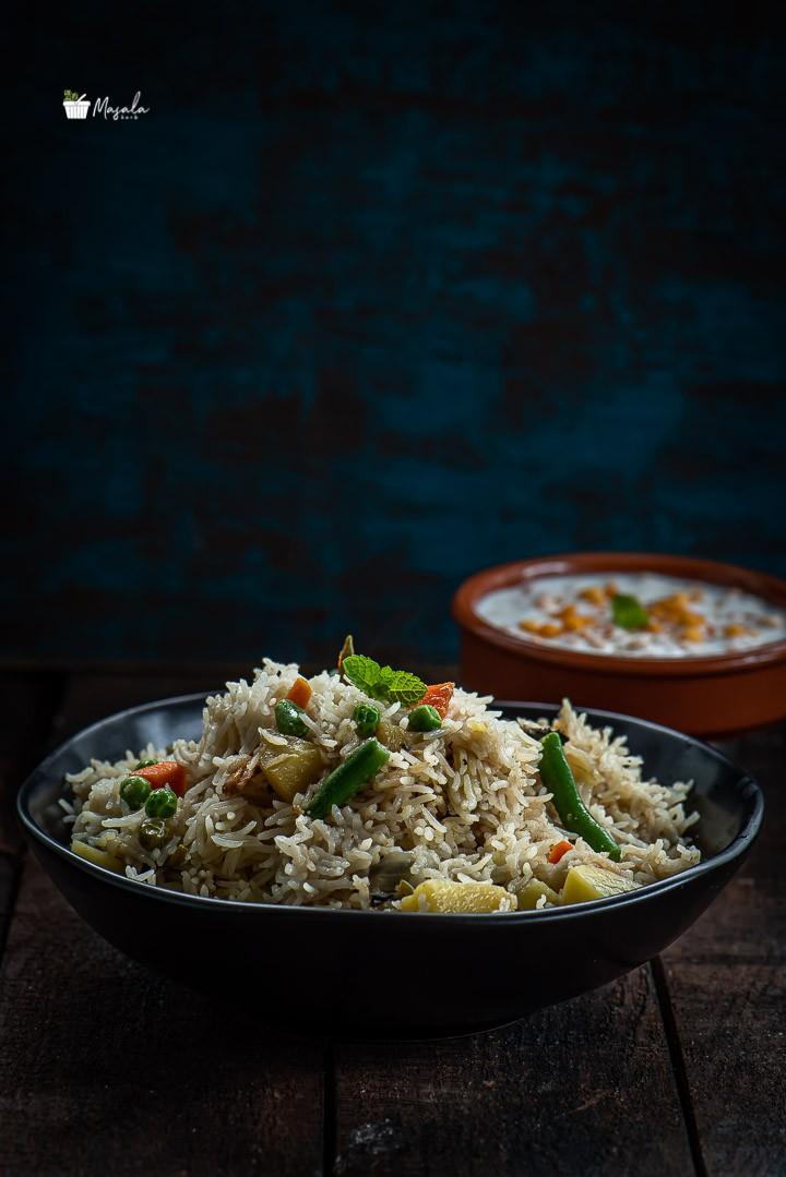Vegetable Biryani served in a black bowl with Boondi Raita on the side.