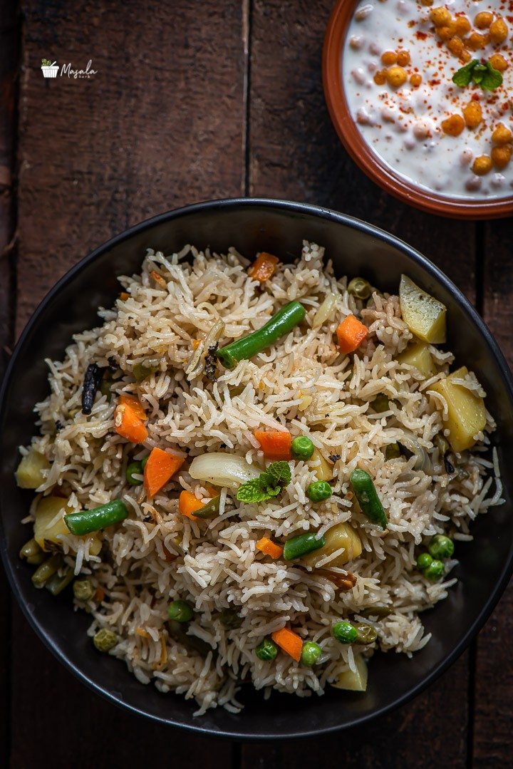 To view of Instant Pot Vegetable Biryani served in a black bowl with Boondi Raita on the side.